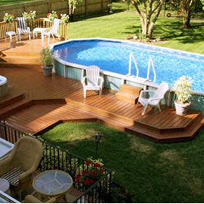 Photo of a backyard. An above ground pool with a multi-layer deck.