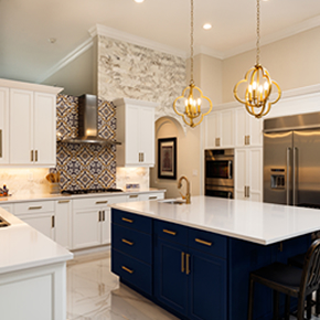 Photo of a kitchen with white cabinets and white counter-tops. Stove has a multi-colored backslash. Kitchen island has blue cabinets with white counter-tops.