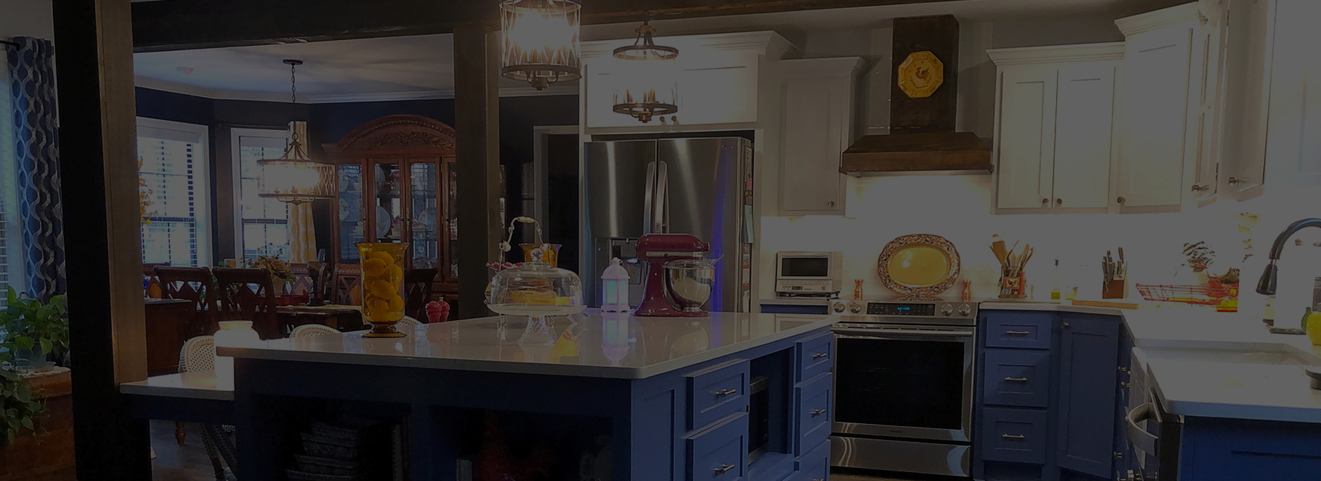 Kitchen and a view of a dinning room. Kitchen has blue lower cabinets, white upper cabinets, and white counter-tops.