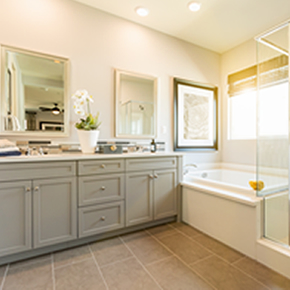Photo of a double vanity beside a bathtub and walk in shower. Cabinets are a light grayish color with white counter-top. Bathtub is white and shower has a clear glass all the way around it.